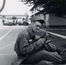 Joe sitting in military fatigues with gun